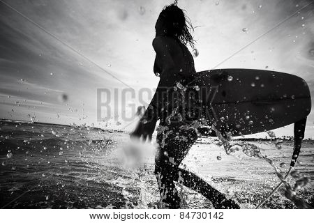 Lady surfer running into sea with surf board