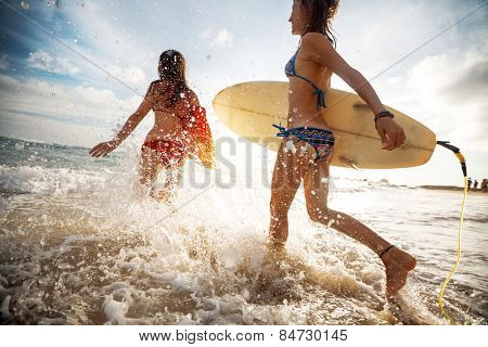 Two young ladies surfers running into sea with surf boards