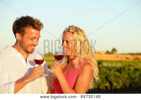 Drinking red wine couple in love. Happy people drinking rose wine alcohol laughing in summer vineyard.
