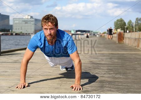 Sport fitness man push-ups. Male athlete exercising push up outside in urban city boardwalk. Fit male fitness model in crossfit exercise outdoors. Healthy lifestyle in Bryggen, Copenhagen, Denmark