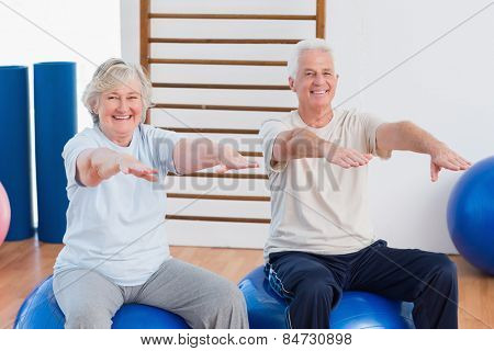 Portrait of senior couple with arms raised sitting on exercise ball at gym