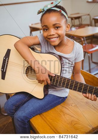 Portrait of cute little girl playing guitar in classroom
