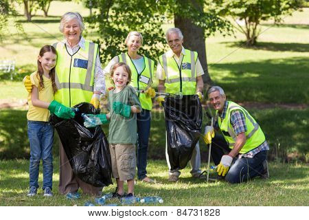 Happy family collecting rubbish on a sunny day