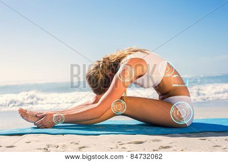 Gorgeous fit blonde in seated forward bend pose on the beach against fitness interface