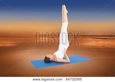 Fit woman stretching body in fitness studio against hazy blue sky