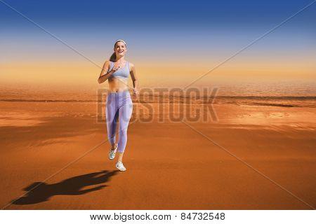 Sporty blonde jogging towards camera against hazy blue sky
