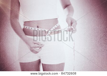 Midsection of woman measuring waist against weathered surface