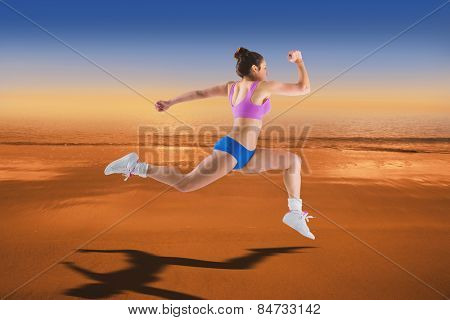 Fit brunette running and jumping against hazy blue sky