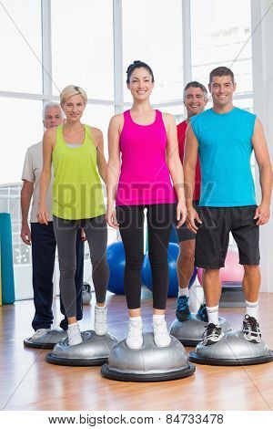 Full length portrait of people standing on balance balls in gym