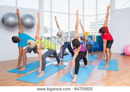 Full length of fit men and women doing stretching exercise at fitness club
