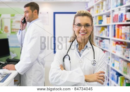 Pharmacist smiling with pharmacist behind on the phone at the hospital pharmacy