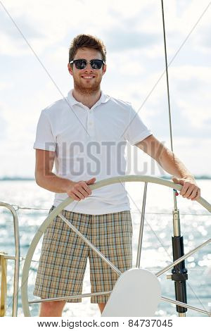 vacation, holidays, travel, sea and people concept - young man in sunglasses steering wheel on yacht