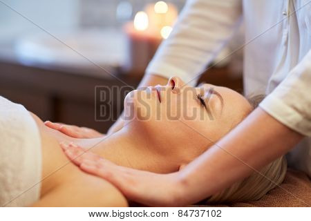 people, beauty, spa, healthy lifestyle and relaxation concept - close up of beautiful young woman lying with closed eyes and having massage in spa