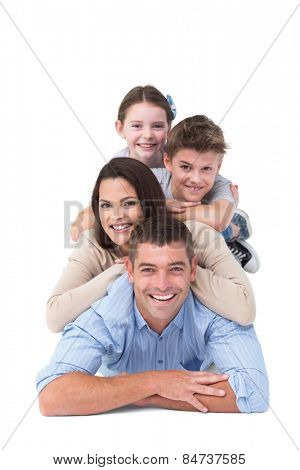 Portrait of happy family lying on top of each other over white background