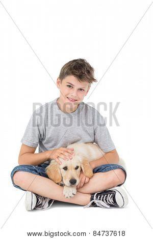 Full length of boy stroking dog while sitting over white background