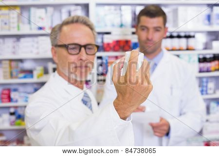 Man holding a box of pills while reading the label in the pharmacy