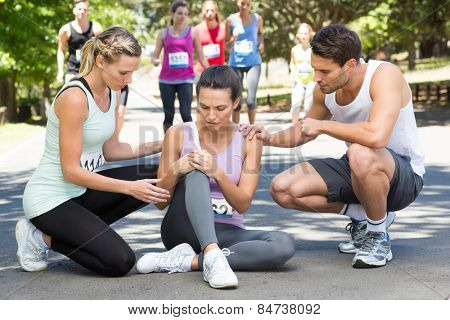 Woman with injured knee during race in park on a sunny day