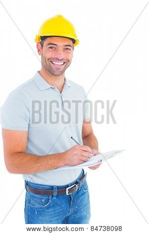 Portrait of smiling male supervisor writing on clipboard on white background