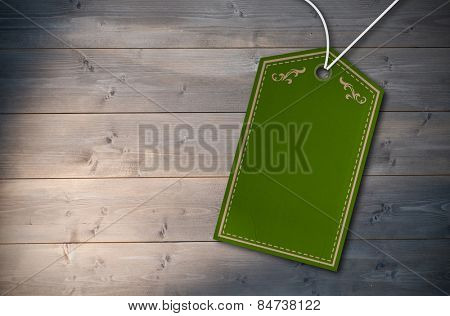 Elegant green and gold tag against bleached wooden planks background