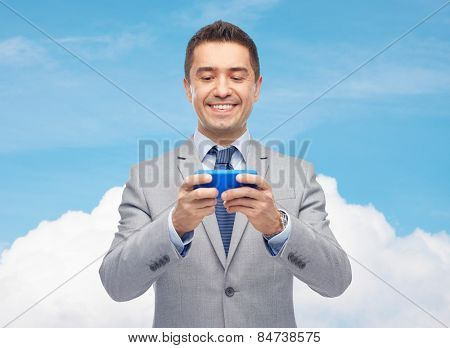 business, people, computing, network and technology concept -happy businessman texting or playing game on smartphone over blue sky and cloud background