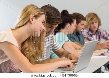 Side view of students using laptop in classroom