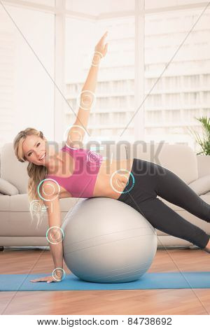 Happy fit blonde doing side plank with exercise ball against fitness interface