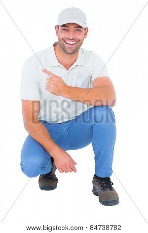 Full length portrait of handyman crouching while pointing on white background