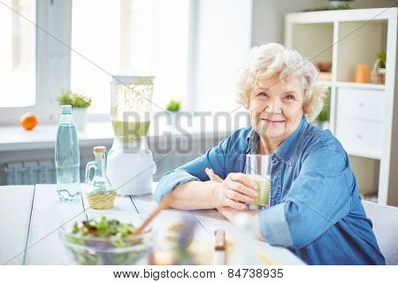 Happy senior female with glass of fruit smoothie looking at camera