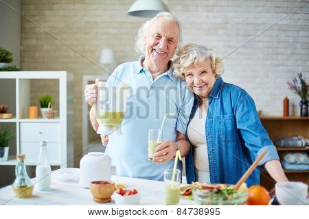 Cheerful seniors looking at camera in the kitchen