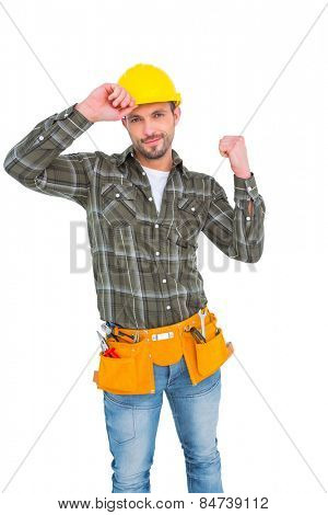 Smiling manual worker clenching fist on white background