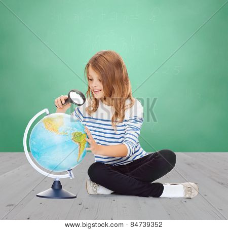 education, childhood, geography and school subject concept - happy little student girl looking at globe with magnifier over green chalk board background