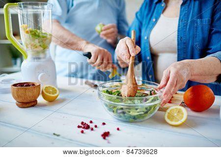 Senior female mixing ingredients of vegetable salad