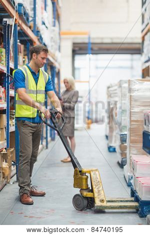 Worker pulling trolley with boxes in warehouse