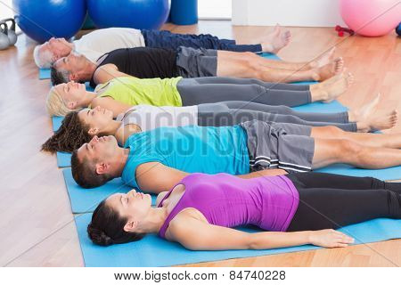 Fit men and women meditating on exercise mats in fitness club