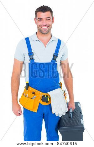 Portrait of happy workman in overalls holding toolbox on white background