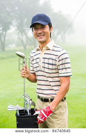 Happy golfer taking club from golf bag at the golf course