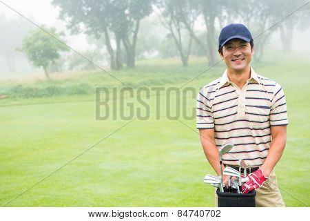 Cheerful golfer smiling at camera holding golf bag at the golf course
