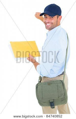 Portrait of smiling postman with letter knocking on white background