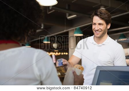 Customer paying by credit card her bread at the bakery