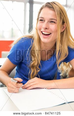 Portrait of cheerful female student writing notes in classroom