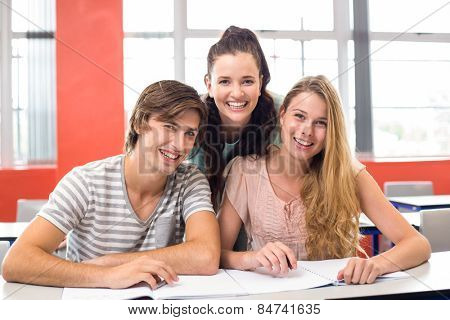 Portrait of happy college students sitting in classroom