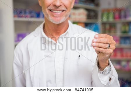 Senior pharmacist holding calling card in the pharmacy