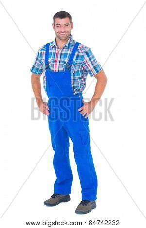 Full length portrait of happy handyman in coveralls standing hands on hip over white background