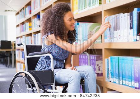 Smiling disabled student in library picking book at the university