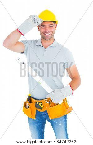 Portrait of smiling handyman holding spirit level on white background