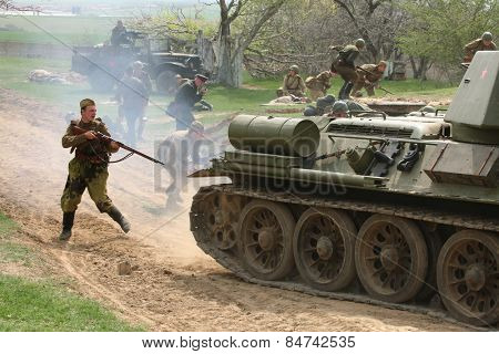 ORECHOV, CZECH REPUBLIC - APRIL 27, 2013: Re-enactors dressed as Soviet soldiers and a Soviet tank T-34 stage an attack during the re-enactment of the Battle at Orechov (1945) Czech Republic.