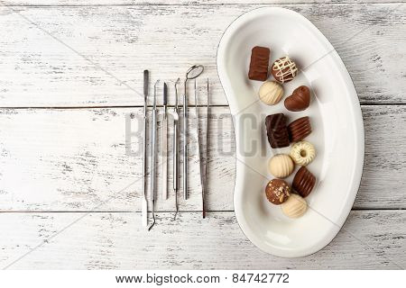 Dentist tools with sweets on tray on wooden background