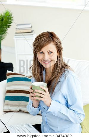 Attractive Businesswoman Drinking Coffee Using Her Laptop
