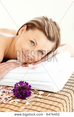 Portrait Of An Attractive Young Woman Lying On Massage Table Smiling