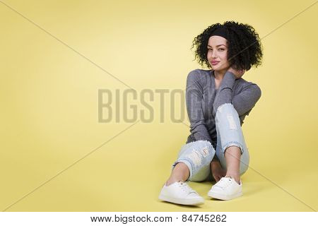 Young woman smiling cute at you on isolated yellow background with empty copy space.